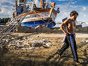 30 APRIL 2013 - MAHACHAI, SAMUT SAKHON, THAILAND:  A Burmese crewman walks away from the fishing trawler he works on after it returned to port in Mahachai, Samut Sakhon province, Thailand. The Thai fishing industry is heavily reliant on Burmese and Cambodian migrants. Burmese migrants crew many of the fishing boats that sail out of Samut Sakhon and staff many of the fish processing plants in Samut Sakhon, about 45 miles south of Bangkok. Migrants pay as much $700 (US) each to be smuggled from the Burmese border to Samut Sakhon for jobs that pay less than $5.00 (US) per day. There have also been reports that some Burmese workers are abused and held in slavery like conditions in the Thai fishing industry.          PHOTO BY JACK KURTZ