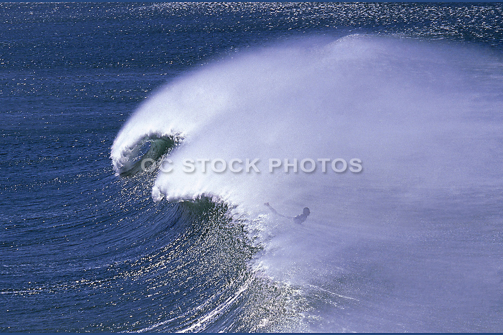 A Surfer In The Ocean Behind A Wave