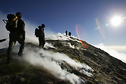 Members of a group of Maltese mountaineers, training for a charity climb up Tanzania's Mount Kilimanjaro, reach the summit of Sicily's Mount Etna, the largest and most active volcano in [Europe], as toxic sulphur fumes spew all around them October 16, 2005. REUTERS/Darrin Zammit Lupi