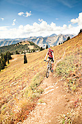 Woman mountain biking outside of Crested Butte, Colorado. Crested Butte is known for miles of singletrack mountain bike trails among beautiful alpine wildflowers.
