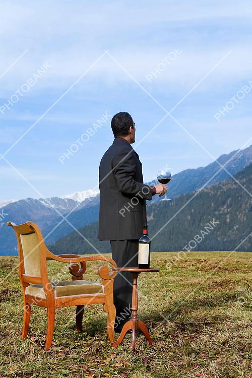 elegant man drinks wine in high altitude