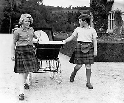 File photo dated 08/09/60 of Princess Anne, 10, and Prince Charles, 11, sharing the task of pulling the pram of baby brother Prince Andrew for a walk in the grounds at Balmoral.