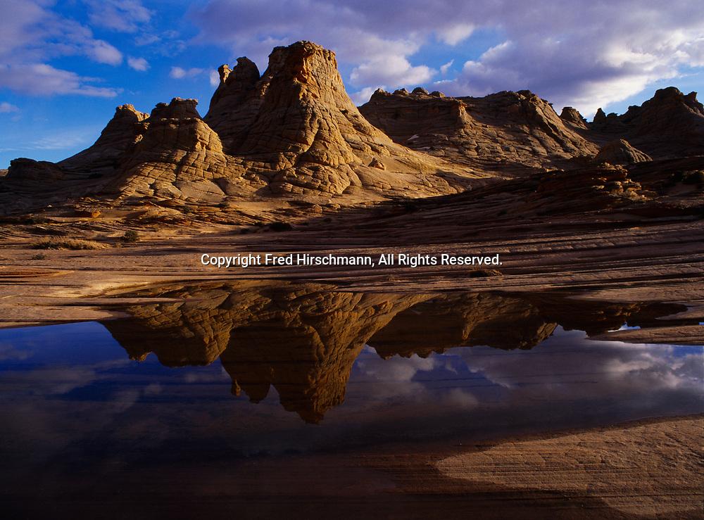Navajo Sandstone beehives reflected in ephemeral slickrock pool, Colorado Plateau in northern Arizona.