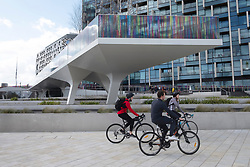 © Licensed to London News Pictures. 27/03/2021. London, UK. Cyclists bike past the new art installation titled Hundreds and Thousands by artist Liz West for The Tide. The outdoor art work is installed on the new elevated riverside trail, The Tide, on the Greenwich Peninsula. 700m of the walkways glass balustrades are covered by a ribbon of colour. Hundreds and Thousands is presented by NOW Gallery.<br />  credit: Ray Tang/LNP