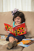 Bibi Salazar looks at a book at her home, March 26, 2014. Salazar's mother, Nelly, is participating in the Home Instruction for Parents of Pre-K Youth (HIPPY) program.