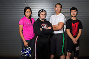 Junior Claire Delacruz, and seniors Jaryle Zamora, Thomas Dao, and Arthur Handy pose for a portrait during wrestling practice at Milpitas High School in Milpitas, California, on December 11, 2015. (Stan Olszewski/SOSKIphoto)