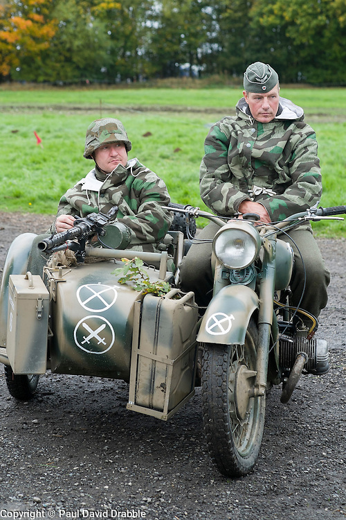 Re-enactors portrayiing troops from the German 276th Volksgrenadier Division on a Motorcycle and side car combination. Both are wearing reversable winter Parka's with the Splinter pattern camoflage showing. An MG34 is mounted on the sidecar The bottom symbol in white idetifies the vehicle is from the 276 Volksgrenadier Division while the Tactical symbol above and on the Motorbike shows it is from the motorcycle messenger platoon.<br /> Pickering Showground during the 1940's Wartime Weekend<br /> <br /> 17/18 October 2015<br />  Image © Paul David Drabble <br />  www.pauldaviddrabble.co.uk