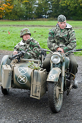 Re-enactors portrayiing troops from the German 276th Volksgrenadier Division on a Motorcycle and side car combination. Both are wearing reversable winter Parka's with the Splinter pattern camoflage showing. An MG34 is mounted on the sidecar The bottom symbol in white idetifies the vehicle is from the 276 Volksgrenadier Division while the Tactical symbol above and on the Motorbike shows it is from the motorcycle messenger platoon.<br />