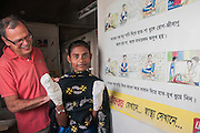 Bangladesh, Jamuna River, (called the Brahmaputra River in India) near the town of Gaibanda. This is the boat based Friendship non-profit organization (NGO), who provide health care and vocational traing  for locals. Dotor Philippe Dubayle (an eye doctor) with a local burn patient.