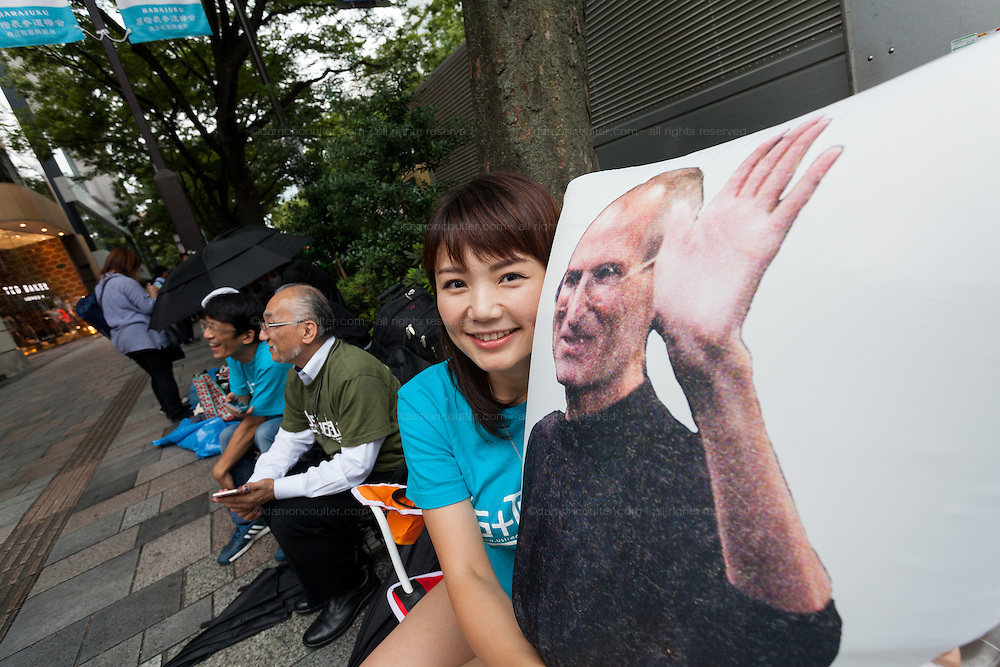 Ayano Tominaga (right) poses with poses with a pillow featuring a picture of Steve Jobs before the launch of the iPhone 7 and iPhone 7 plus at the Apple store in Omotesando, Tokyo, Japan. Friday September 16th 2016. The iPhone launches are global events. Around 200 eager customers waited outside the Apple store in Tokyo, some for several days, to be first in line to buy the new product.