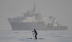 © Licensed to London News Pictures. 29/11/2020. Swansea, UK. A paddle boarder is pictured in the sea passing a ship off the coast of Swansea at the end of beautiful day in Wales and across the UK. Photo credit: Robert Melen/LNP