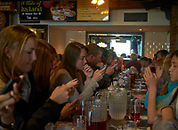 Students at a Pub Lunch in Dublin. After being internet deprived for 24 hours. No Beer - Just Smart Phones. Image taken with a Fuji X-T1 camera and 27 mm f/2.8 lens (ISO 800, 27 mm, f/2.8, 1/38 sec). Raw image processed with Capture One Pro and Nik Define 2, and Photoshop CC.
