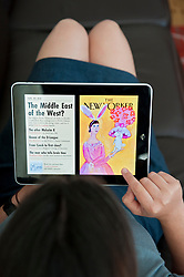 close up of woman using iPad digital tablet computer to read The New Yorker magazine