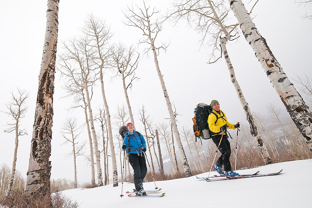 Backcountry skiers Judd MacRae and Emily Miller travel down a jeep road lined with aspen trees in Uncompahgre National Forest, Colorado.