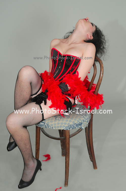 Young sexy woman in red and black corset and fishnet stockings