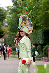 A racegoer wears a hat adorned with a horse during day one of Royal Ascot at Ascot Racecourse
