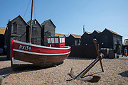 A bright red fishing boat and anchor, part of the Hastings Fishermens Museum, on the 20th April 2019 in Hastings in the United Kingdom. The Hastings Fishermens Museum is a museum dedicated to the fishing industry and maritime history of Hastings.