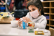 17 FEBRUARY 2021 - DES MOINES, IOWA: A kindergarten student opens her breakfast milk carton in the classroom at Walnut Street School in downtown Des Moines. To reduce crowding and improve social distancing the school is serving meals in the classrooms. Students are required to wear masks unless they're eating. Des Moines Public Schools (DMPS) opened to in person education this week after teaching most of the 2020-2021 school year either remotely or with a hybrid/remote learning model. The district has ended its hybrid model. The Governor of Iowa has aggressively pushed schools to return to in person education, going so far as to threaten to withhold funds from districts that don't return to in person classes. DMPS, the largest school district in Iowa, has resisted the Governor's push because Polk County, IA, has been a Coronavirus/COVID-19 hotspot with positivity rates well above 10 percent. The district was recently able to vaccinate many teachers and positivity rates have fallen to 9 percent, making it safer to reopen schools.    PHOTO BY JACK KURTZ