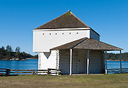The second story of the Guard House is mostly original, but the lower part has been rebuilt due to tidal weathering, at English Camp, Garrison Bay, San Juan Island National Historic Park, Washington. The Pig War 1859-1872 peacefully arbitrated the San Juan Islands into the territorial United States.