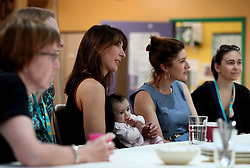 Samantha Cameron holds a young baby as she hosts a coffee morning to celebrate the work of charity KIDS and the services that they deliver to disabled children, young people and their families, at Hackney Adventure Playground in London.