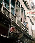 Young girls standing on balcony overlooking street, Lucknow, Uttar Pradesh, India
