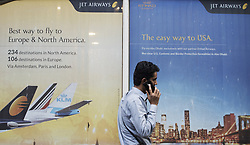 March 27, 2019 - Kolkata, West Bengal, India - A man talks over a phone as he walks past Jet Airways poster in Kolkata, India on 27 March, 2019.  Jet Airways told the government that they will start operating 75 aircraft by the end of April instead of 35 which is at present according to the Indian media report. (Credit Image: © Indranil Aditya/NurPhoto via ZUMA Press)