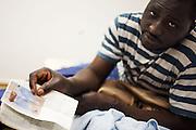 Un ragazzo mostra i suoi documenti. Interno ex palazzine olimpiche.