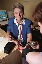 Doctor in community paediatric health centre sitting at desk taking patient's blood pressure and using stethoscope to monitor her pulse,