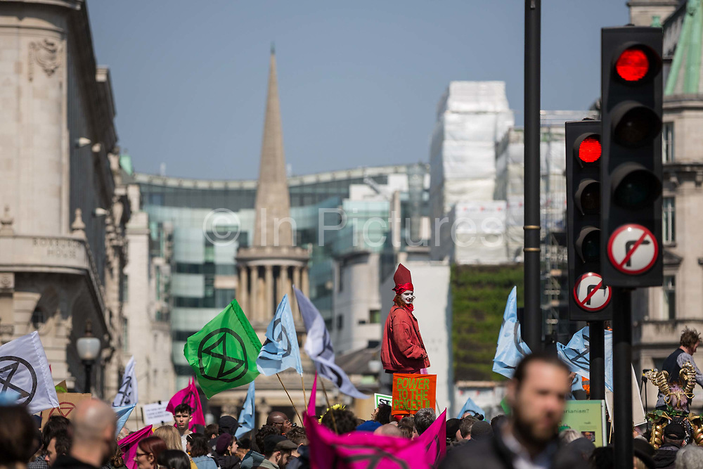 A woman in a red costume stands on a stage surrounded by flags depicting the logo of Extinction Rebellion during a protest against climate change in the middle of Oxford Circus on 15th April, 2019 in London, United Kingdom.  Extinction Rebellion have blocked five central London landmarks in protest against government inaction on climate change. .