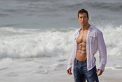 muscular man with an open shirt exposing his ripped hot smooth body at the ocean