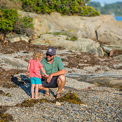 A man and his young daughter explore the shoreline on East Gosling Island in Casco Bay, Harpswell, Maine.
