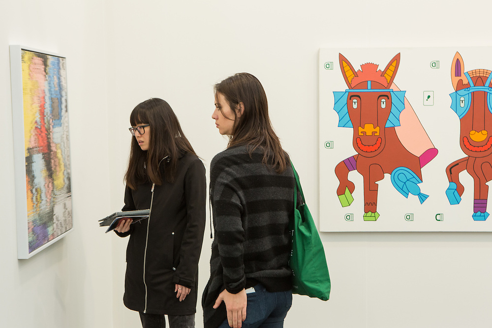 "New York, NY - 6 May 2016. Frieze New York art fair. Two women look at a gallery painting. Behind them is Karl Wirsum's ""I swallowed the former mule formula""."