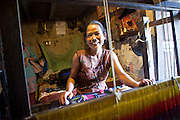 A Nepalese woman laughs and smiles as she operates a tapestry loom in her home.  She is able to provide for her family from selling rugs and carpets and her sons have been able to return to school education.  She was assisted to buy the loom by Voice of Children charity.