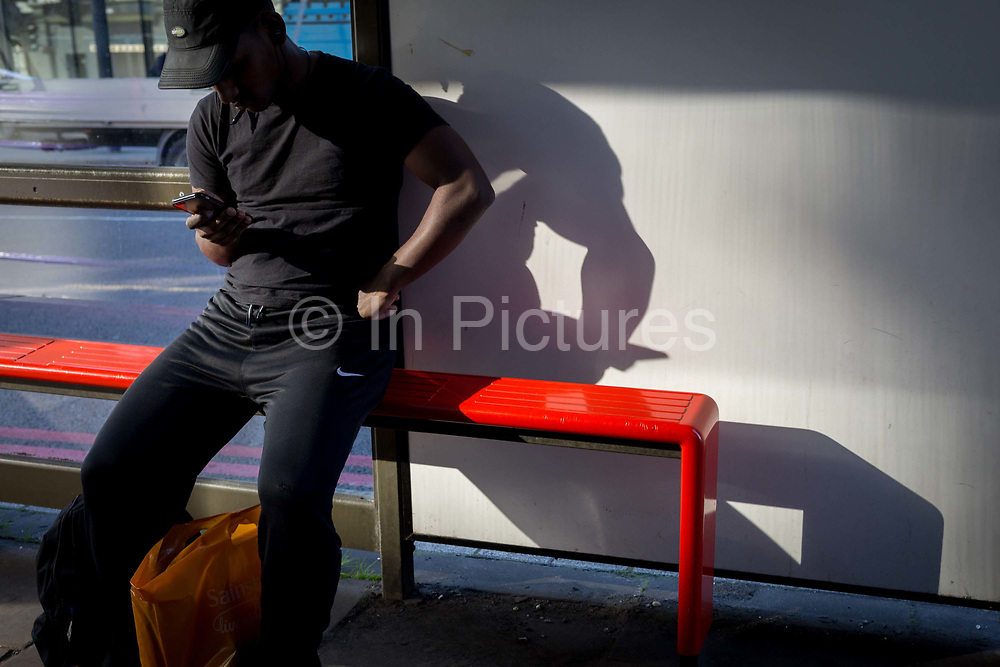 A youth at a Southwark bus stop checks messages on his mobile phone, on 26th September 2018, in London, England.
