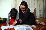 Aghele Rezaie, 30, (right) the famous Afghan actress who has taken part in the controversial movie 'At Five in the Afternoon' (Winner of the Cannes Film Festival Jury Prize in 2003) is helping her son, Tamim, 8, (left) with his daily homework in their home in Kabul, Afghanistan. 'At Five in the Afternoon' focuses on the life of a progressive young woman who dreams of growing up to become the President of the Republic despite her oppressive home life and a strained relationship with her bigoted but loving father. The film follows the daily struggles of Afghan women in post-Taliban Afghanistan with tenderness and hope against a tragic background of death and despair.