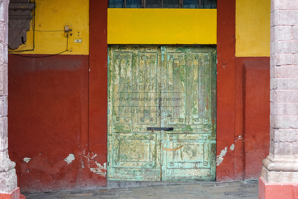 An old wooden door painted green in the Plaza Allende in San Miguel de Allende, Guanajuato, Mexico.