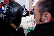 Old ex wrestlers backstage looking at magazine from the past. Lucha Libre wrestling origniated in Mexico, but is popular in other latin Amercian countries, including in La Paz / El Alto, Bolivia. Male and female fighters participate in the theatrical staged fights to an adoring crowd of locals and foreigners alike.