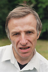Portrait of man with learning disabilities standing outdoors looking serious,