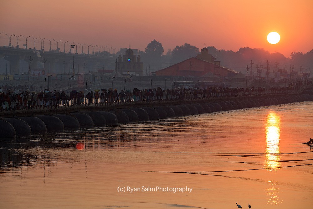 As down breaks over the Ganges, just upriver from the holy Sangam, Hindu pilgrims make their way to bathing points along the river. Kumbh mela