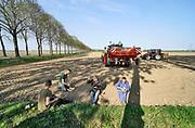 Nederland, Batenburg, 17-4-2020 Een boer, loonwerker, poot aardappels. Het gebeurt automatisch via een ingenieus mechaniek achter de tractor.  De grond is droog door het drie weken uitblijven van regen.Foto: Flip Franssen