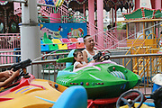 Kids and their parents sit for a ride at a small amusement park in the new district of Yangzhou, Jiangsu Province, China on 19 July 2012. While the Chinese government has tried various ways to cool down the property market, real estate prices have still seen a steady increase in recent years, proving hard for the country to move away from an investment driven economy.