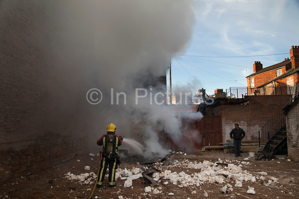 Smoke billowing into the sky from a fire in the Jewellery Quarter as a fireman from the emergency services put out the small blaze in Birmingham, United Kingdom. On investigation this fire turned out to be a man burning polystyrene behind a business, presumably to save on the hassle of recycling such a large volume.