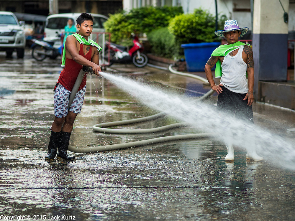14 AUGUST 2015 - BANGKOK, THAILAND:  A workers hoses down the pavement in Saphan Pla fish market in Bangkok. Saphan Pla fish market is the wholesale fish market that serves Bangkok. Most of the fish sold in Saphan Pla is farmed raised fresh water fish. The market is open 24 hours but it's busiest in the middle of the night and then again from about 7.30 until 11 in the morning.       PHOTO BY JACK KURTZ