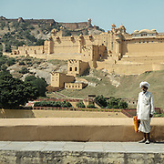 An old rajasthani man stands next to the Amber fort.