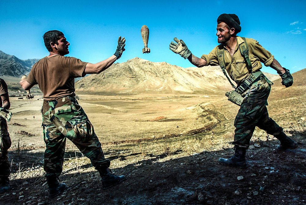 """2/24/04 -- SPECIAL FORCES A-TEAM -- ORUZGAN PROVINCE, AFGHANISTAN --  Soldiers of the newly formed Afghan National Army, 1ST Company of the First Battalion, Third  Brigade led into the Oruzgan Province by an A-TEAM with the 3rd Special Forces Group toss an 82mm mortar while working hand in hand with Special Forces soldiers in a human chain moving nearly ten tons of munitions from a bunker complex under the Oruzgan district headquarters into rented """"jingle"""" trucks. Special Forces A-Team and officers of the Afghan National Army, 1ST Company of the First Battalion, Third  Brigade spent an entire day and night applying  """"Afghan Diplomacy"""" by drinking many glasses of tea and finally asking what is behind the locked doors in the bunkers below. Ubai Dullah's response was, """"Nothing for soldiers.....just some bullets....""""  After initial inspection of the bunkers, nearly ten tons of mortars, rockets, land mines and ammunition were found in the bunkers.  Negotiations between the district chief and the A-Team came to brief but tense """"stand off"""" as soldiers began to remove the weapons when the district chief called in armed militia. Between talks and calling in an U.S. Air Force B-1 Bomber to make low passes over the valley, matters were resolved with some ammunition allowed to stay in the hands of the district chief but all mortars and rockets had to be surrendered. (Photo by Jack Gruber, USA TODAY)"""