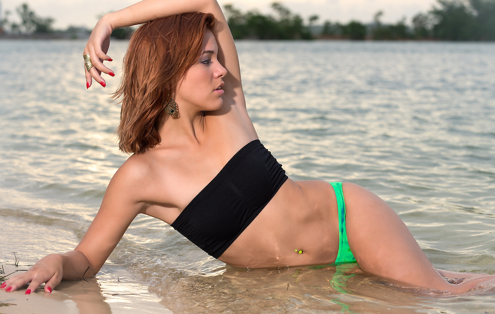 Young caucasian woman enjoys a morning in the beach laying in the ocean and looking away.