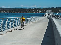 United States, Washington, Kirkland, male cyclist on 520 floating bridge over Lake Washington