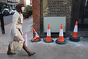 Woman walking past some traffic cones, one of which apprears to be leaning towards her. Central London, UK.