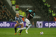 Cheikhou Kouyate of West Ham utd ®  battles with Aaron Mooy of Huddersfield town . Premier league match, West Ham Utd v Huddersfield Town at the London Stadium, Queen Elizabeth Olympic Park in London on Monday 11th September 2017.<br /> pic by Kieran Clarke, Andrew Orchard sports photography.