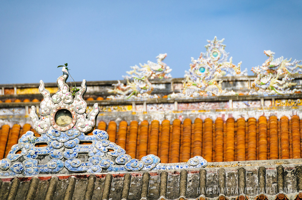 Ornate roof decorations at the Imperial City in Hue, Vietnam. A self-enclosed and fortified palace, the complex includes the Purple Forbidden City, which was the inner sanctum of the imperial household, as well as temples, courtyards, gardens, and other buildings. Much of the Imperial City was damaged or destroyed during the Vietnam War. It is now designated as a UNESCO World Heritage site.